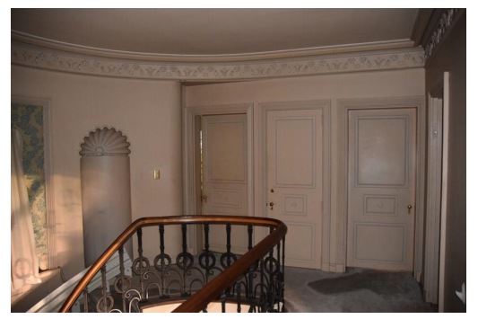 Notable rooms include the entrance hall with a curving staircase, that opens into a living room and dining room. All lavishly adorned with high-relief plaster trim.